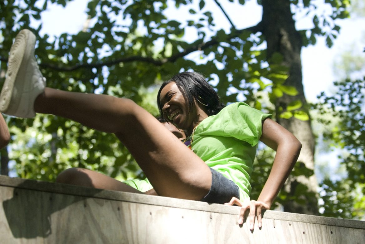 A teen camper climbs over a wall during Chesapeake Life Center's annual Camp Phoenix teen grief camp.