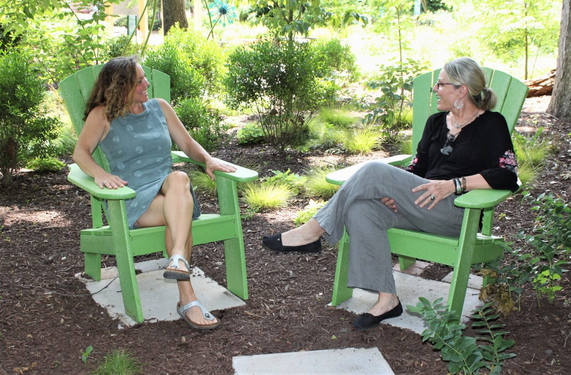 Hospice of the Chesapeake Integrative Arts Volunteers Jill Madey, left, and Teri Jacobson, share a laugh and a smile with each other, as they so often do as friends and partners. They are pictured in a shady spot in the Children's Memorial Garden.