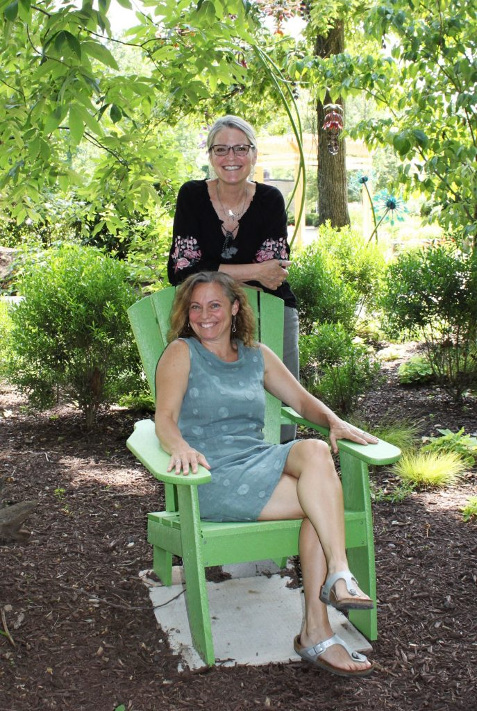 Hospice of the Chesapeake Integrative Arts Volunteers Jill Madey, left, and Teri Jacobson, are pictured in a shady spot in the Children's Memorial Garden.