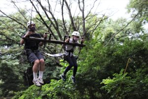 From left, Jeremiah Faust and Lillian Cross ride in a swing that flies high into the tree canopy during Camp Phoenix Teen Grief Camp held at Terrapin Adventures in Savage, Maryland.