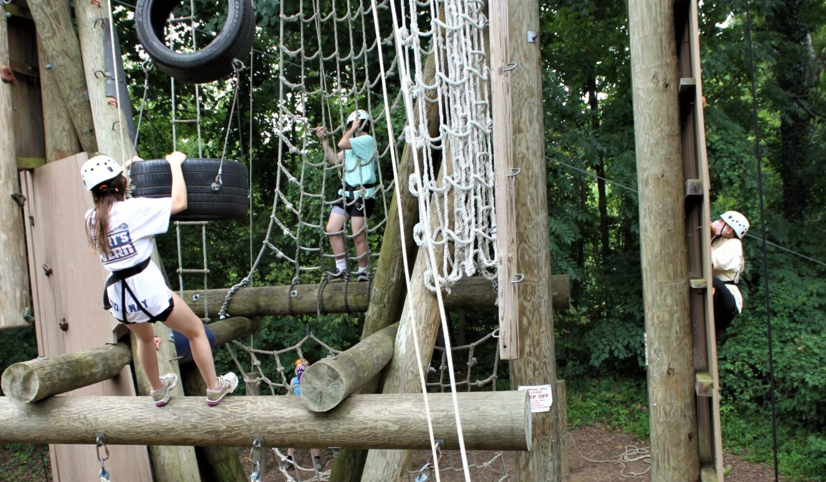 Three campers scale different sections of climbing apparatus while participating in Camp Phoenix Teen Grief Camp Aug. 15 at Terrapin Adventures in Savage, Maryland.