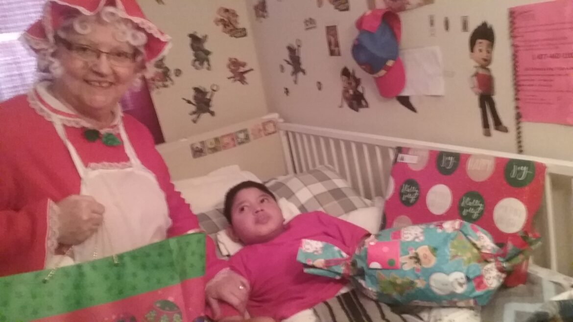 Hospice of the Chesapeake Volunteer Alice Jo Weaver, dressed as Mrs. Santa, to deliver gifts to a pediatric hospice patient Diego Medrano Alvarado and his family.
