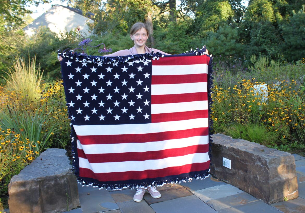 Averie Mortimer holds up one of the no-sew patriotic blankets she created and then donated to our We Honor Veterans program.