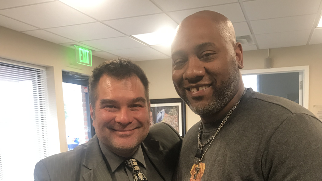Eric Bush, MD, poses with his patient of 8 years, Brian Thompson, in the Hussman Supportive Care Center on the John & Cathy Belcher Campus in Pasadena, Maryland.